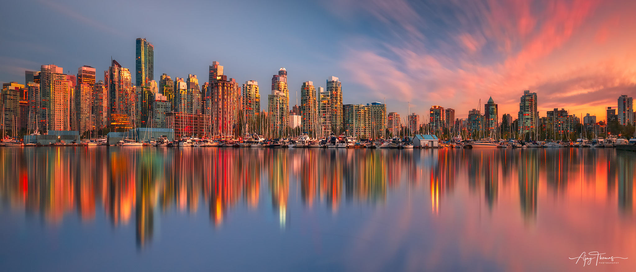 A panoramic view of Vancouver city skyline reflections during sunset.  A long exposure shot from Stanley park,vancouver